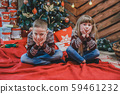 Cute siblings are sitting on floor of stylish room, looking bored and upset. 59461232
