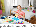 girl with color paper sitting at table at home 59466570