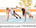 women making high five in side plank on sport mats 59466608