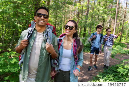 group of friends with backpacks hiking in forest 59466757