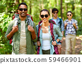 group of friends with backpacks hiking in forest 59466901