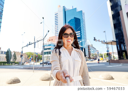 asian woman taking picture by selfie stick in city 59467033