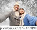 happy couple in winter clothes taking selfie 59467099