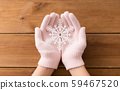 hands in pale pink gloves holding big snowflake 59467520