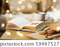 book with autumn leaf, cookies and tea on table 59467527