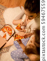 happy female friends eating pizza at home 59467559