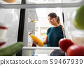 happy woman taking juice from fridge at home 59467939