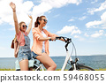 teenage girls or friends riding bicycle in summer 59468055