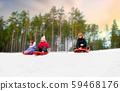 kids sliding on sleds down snow hill in winter 59468176