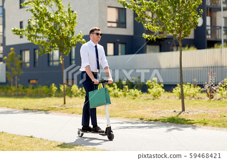 businessman with shopping bag riding scooter 59468421