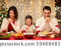 family praying before meal at christmas dinner 59468483