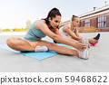 women with fitness trackers stretching outdoors 59468622