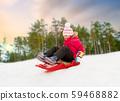 happy little girl sliding down on sled in winter 59468882
