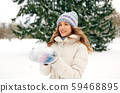 smiling woman with snow in winter forest 59468895