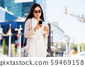 smiling woman with smartphone and coffee in city 59469158