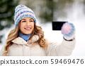 woman taking selfie by smartphone in winter 59469476