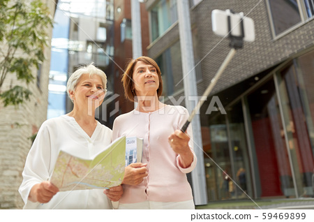 senior women with map and city guide taking selfie 59469899