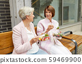 senior women eating takeaway food on city street 59469900