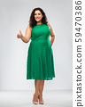 happy woman in green dress showing thumbs up 59470386