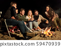 friends with tablet pc at night camp fire on beach 59470939