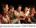 happy friends with sparklers at night outdoors 59470956