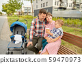 family with baby in stroller and coffee in city 59470973