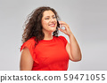 smiling woman in red dress calling on smartphone 59471055