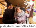 senior couple at christmas market souvenir shop 59471445
