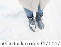 female feet in winter shoes on snow from top 59471447