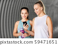 women or female friends with smartphone and flask 59471651
