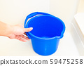 Hand holding a bucket 59475258