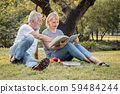 Grandfather and grandmother read a book sitting on 59484244