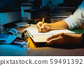 Businessman writing on document while working late in office. 59491392