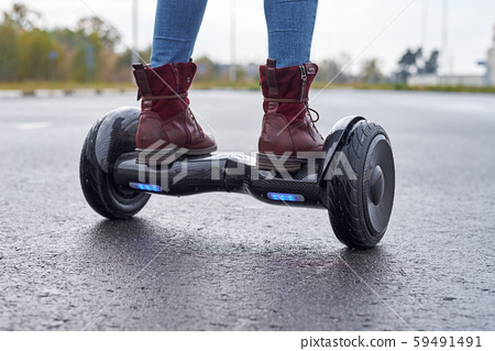 Close up of woman using hoverboard on asphalt 59491491