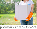 Woman with white t-shirt hold white box filled with plastic bottle 59495274