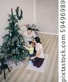 family sitting near the Christmas tree 59496989