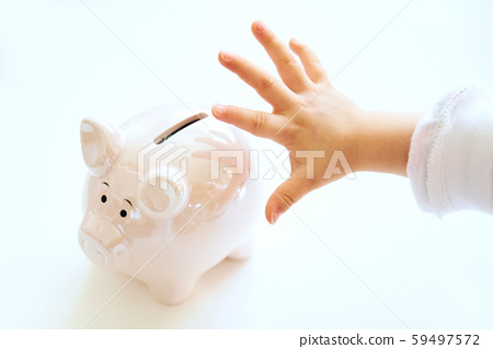 Baby hand reaching for savings in pink piggy bank 59497572