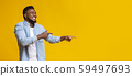Joyful black guy pointing two fingers aside at copy space 59497693