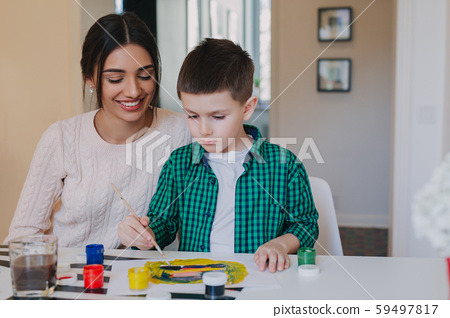 Mother and little son together paint at home. Woman helps her child 59497817