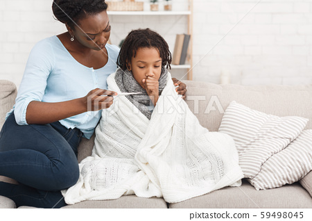 Mother measuring temperature of her sick daughter with thermometer 59498045