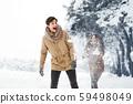 Girlfriend Throwing Snow At Boyfriend Walking In Forest 59498049