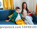 Beautiful Indian woman sitting on sofa and reading a book to her cute son 59498100