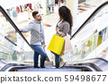 Happy couple with shopping bags rising on escalator 59498677