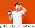 Worried awake teen boy with alarm clock 59499054