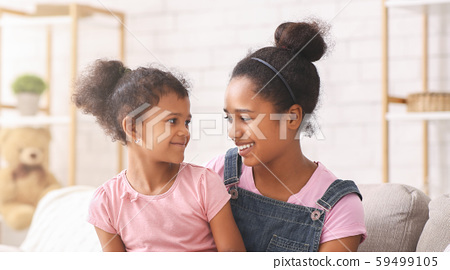 Happy african american sisters smiling to each other 59499105