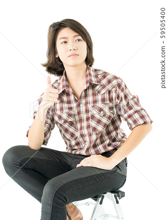 Young woman in a plaid shirt posing in studio on 59505400