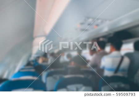 Blurred defocused image of many people on passageway and looking for seat in the planes. Stock photo image of blurry background of passengers, travelers in airplane ready to fly or landing 59509793