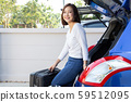 Young Asian woman packing suitcases into the trunk 59512095