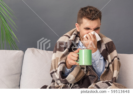 Feeling Sick. Young man sitting on sofa under blanket studio isolated on grey with cup of tea 59513648