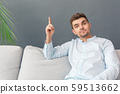 Freestyle. Young man studio sitting on sofa isolated on grey pointing up creative idea smiling wise 59513662